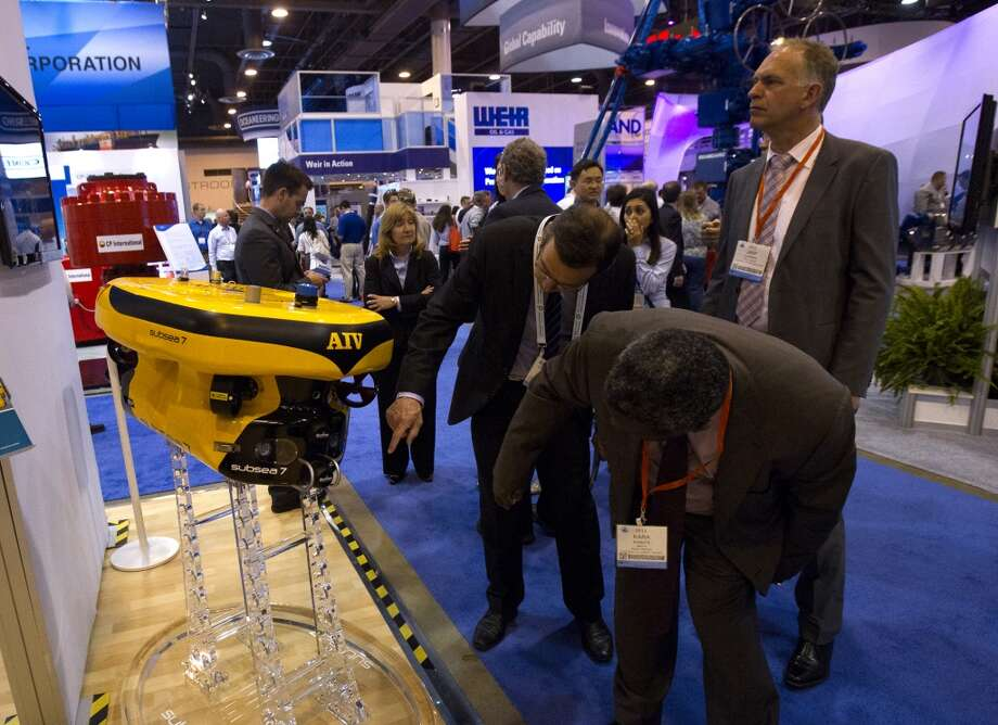 Spectators look at an, AIV, or Autonomous Inspection Vehicle made by Subsea 7, is seen at the company's booth during day two of the Offshore Technology Conference at Reliant Center Tuesday, May 7, 2013, in Houston. The vehicle is used to conduct inspections at on subsea systems at depths of up to 10,000 feet. (Cody Duty / Houston Chronicle) Photo: Cody Duty, Houston Chronicle