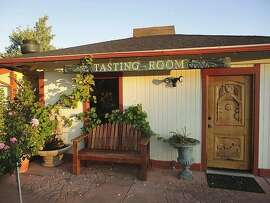 At Sunce Winery, a small white panel-trimmed cottage that serves as the tasting area is nearly swallowed up by luscious heritage rose bushes.