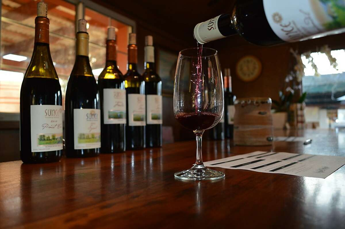 A glass of wine is poured in the Sunce Winery tasting room.