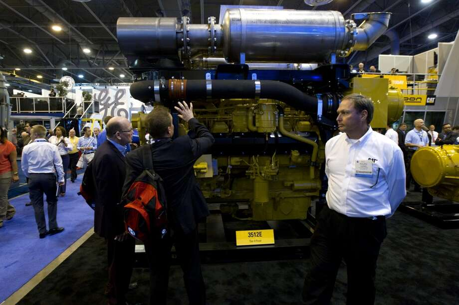 Attendees look at a Caterpillar Tier 4 Final is seen during day two of the Offshore Technology Conference at Reliant Center Tuesday, May 7, 2013, in Houston. (Cody Duty / Houston Chronicle) Photo: Cody Duty, Houston Chronicle