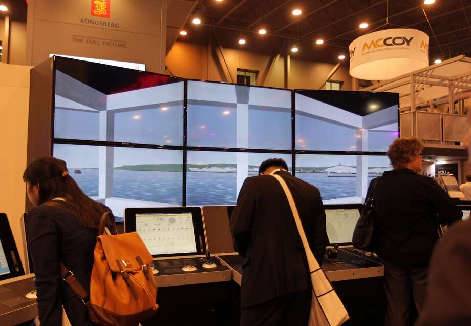Conventioneers look over a row of video screens at the Kongsberg Oil & Gas Technologies Inc. during OTC 2013 at Reliant Park Tuesday, May 7, 2013, in Houston. ( James Nielsen / Houston Chronicle ) Photo: James Nielsen, Houston Chronicle