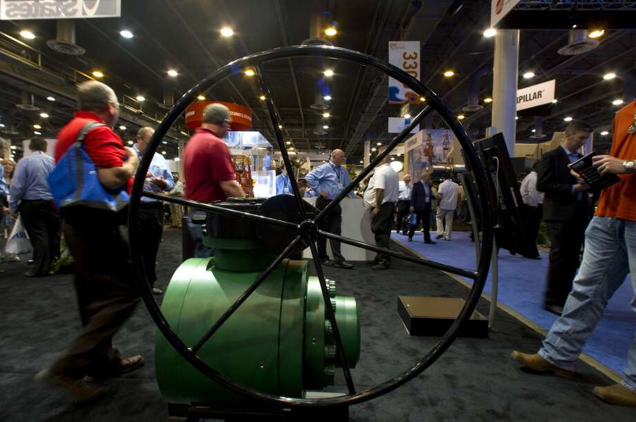 Attendees walk past a ball valve during day two of the Offshore Technology Conference at Reliant Center Tuesday, May 7, 2013, in Houston. (Cody Duty / Houston Chronicle) Photo: Cody Duty, Houston Chronicle