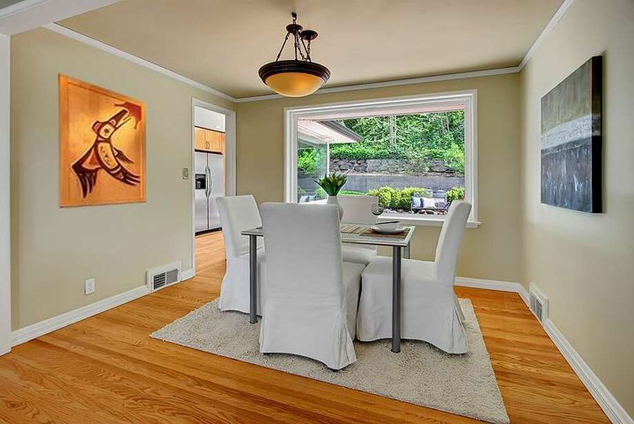 Dining room of 3516 31st Ave. W. The 1,860-square-foot mid-century modern home, built in 1951, has three bedrooms, 1.75 bathrooms, an updated kitchen, a family room with a fireplace and a big deck on a 5,880-square-foot lot. It's listed for $558,888. Photo: Courtesy Bruce Phares And Mark Besta, Windermere Real Estate