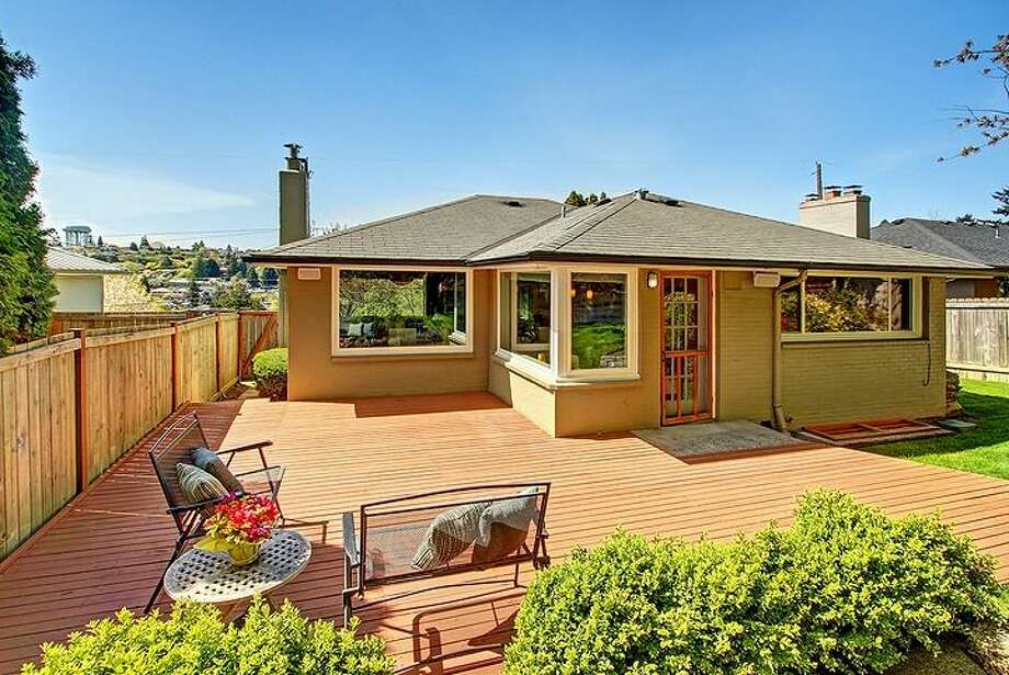 Deck of 3516 31st Ave. W. The 1,860-square-foot mid-century modern home, built in 1951, has three bedrooms, 1.75 bathrooms, an updated kitchen and a family room with a fireplace on a 5,880-square-foot lot. It's listed for $558,888. Photo: Courtesy Bruce Phares And Mark Besta, Windermere Real Estate