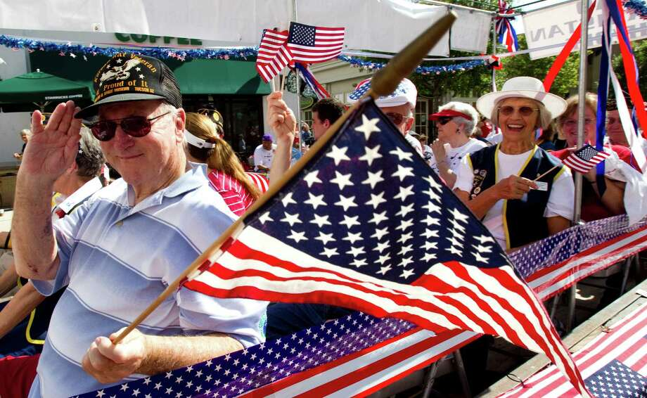 Korean War veteran Ducky Drake salutes as he rides in the annual Fourth of July Parade at last year's July 4 event in The Woodlands. Photo: Brett Coomer, Houston Chronicle / 2012 Houston Chronicle