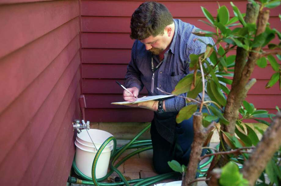 Health Department Lab Technician Jason Glenn collects a water sample from a home on Lolly Lane in Stamford, Conn., on Tuesday, May 7, 2013. Photo: Lindsay Perry / Stamford Advocate