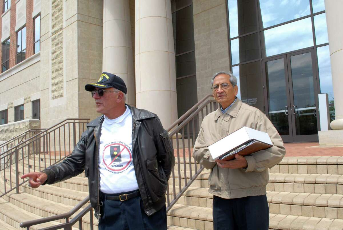 Helwig F. Van Der Grinten, left, and Ray Patel stand on the steps of Sugar Land City Hall before they present petitions asking the city to allow voters to decide the future of the red-light camera program.Helwig F. Van Der Grinten, left, and Ray Patel stand on the steps of Sugar Land City Hall before they present petitions asking the city to allow voters to decide the future of the red-light camera program.