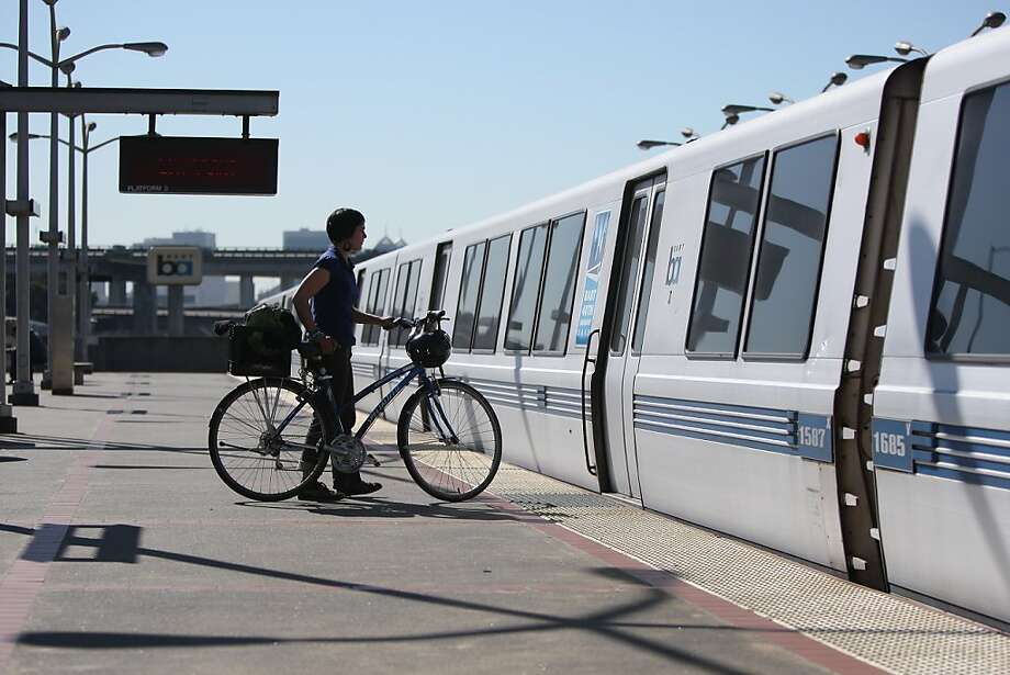 Angela Entzel takes her bike on a train at the MacArthur Station in February. A BART survey found a majority of riders favor expanding access for bikes. Photo: Jessica Olthof, The Chronicle