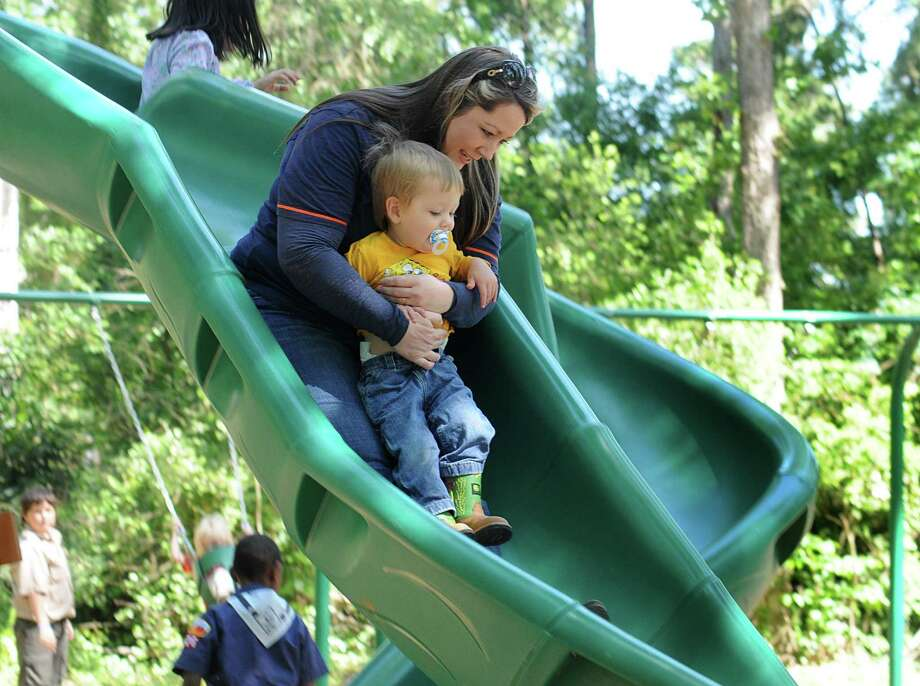 Kelly Fikes and her son, Cooper, try out the new slide during the grand re-opening of Sycamore Spring Park on Sycamore Springs in Kingwood. The Elm Grove Village Association renovated the playground with activities for children and adults. Photo: David Hopper, Freelance / freelance