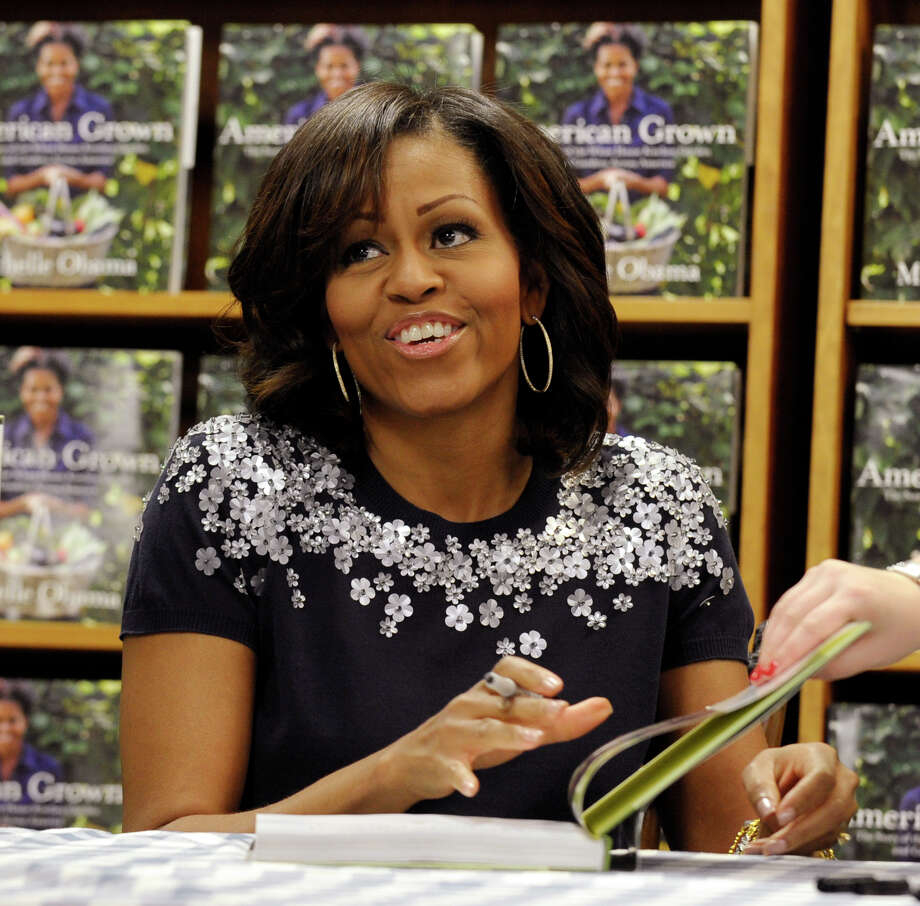 "First lady Michelle Obama signs copies of her book ""American Grown: The Story of the White House Kitchen Garden and Garden Across America"" at the Politics & Prose bookstore in Washington, Tuesday, May 7, 2013. (AP Photo/Susan Walsh) Photo: Susan Walsh"