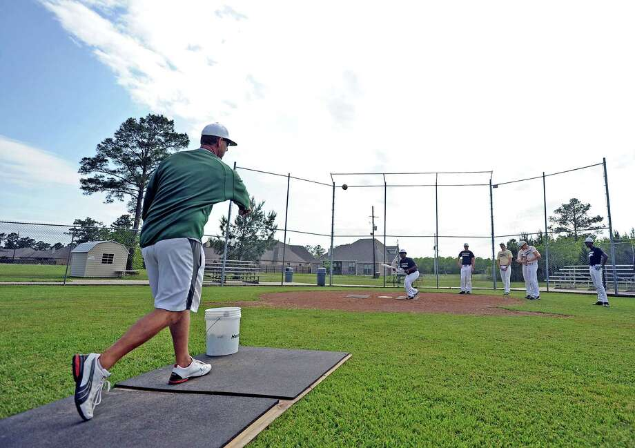 Legacy Christian Academy baseball coach Chris Fackler, left, works with his team at the plate during practice on Thursday, April 25, 2013. Photo taken: Randy Edwards/The Enterprise Photo: Randy Edwards