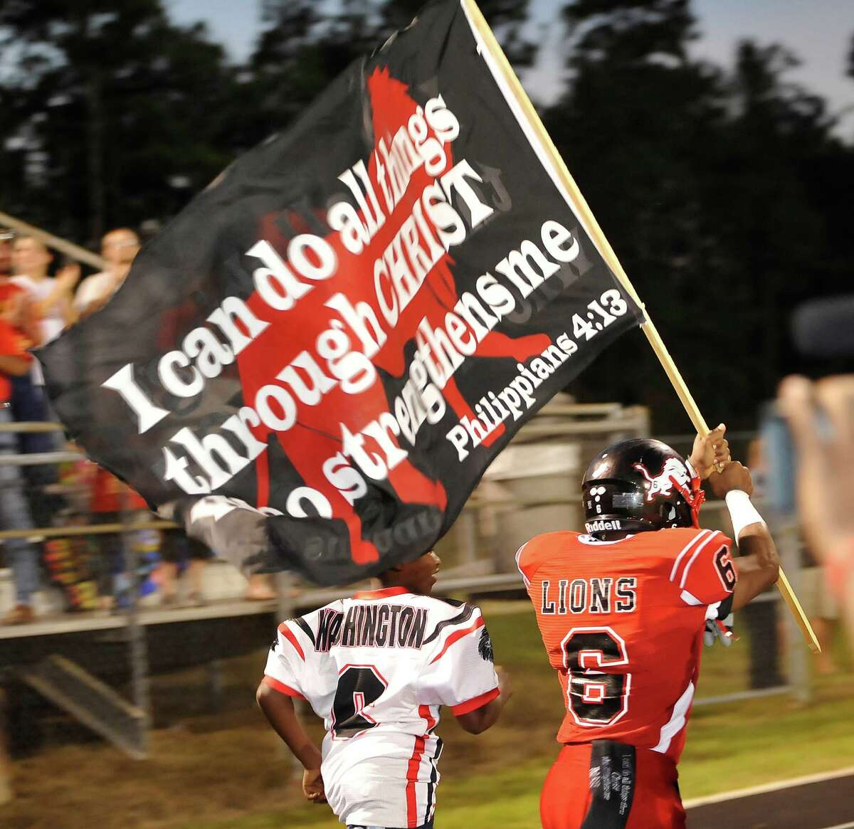 Kountze football player #6 Jamazdon Powell carries a flag as the team comes into the stadium. This was the first home football game in Kountze since the sign controversy started and since the Thursday hearing that determined the cheerleaders could or could not use their faith-based signs. Dave Ryan/The Enterprise