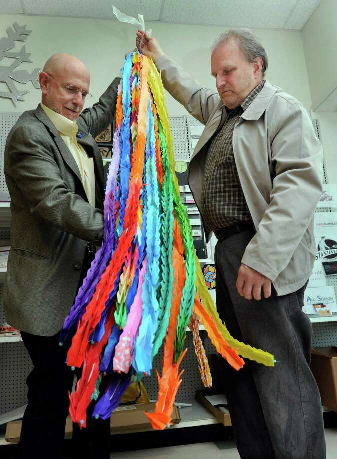 Martin Swist of Tokyo, Japan, left, and Ray Horvath, a teacher in the before and after program at Sandy Hook Elementary School, hold a sculpture of 1,000 origami cranes, made and donated to Sandy Hook by families in Tokyo and students at The American School in Japan, Monday, May 6, 2013. Photo: Carol Kaliff / The News-Times