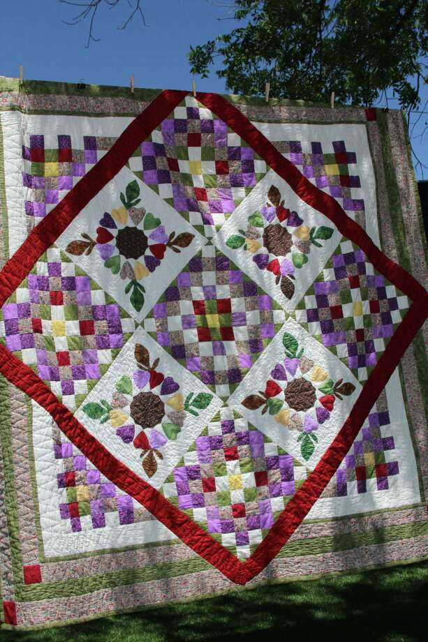 "Haupstrasse Quiltfest was held on Boerne's Main Plaza and throughout downtown Saturday, with quilt shows, sales and demonstrations and displays in retail store windows. ""Wreath of Hearts"" was sewn by Minnie Gatica. Photo: Lauri Gray Eaton / Northwest Wee"