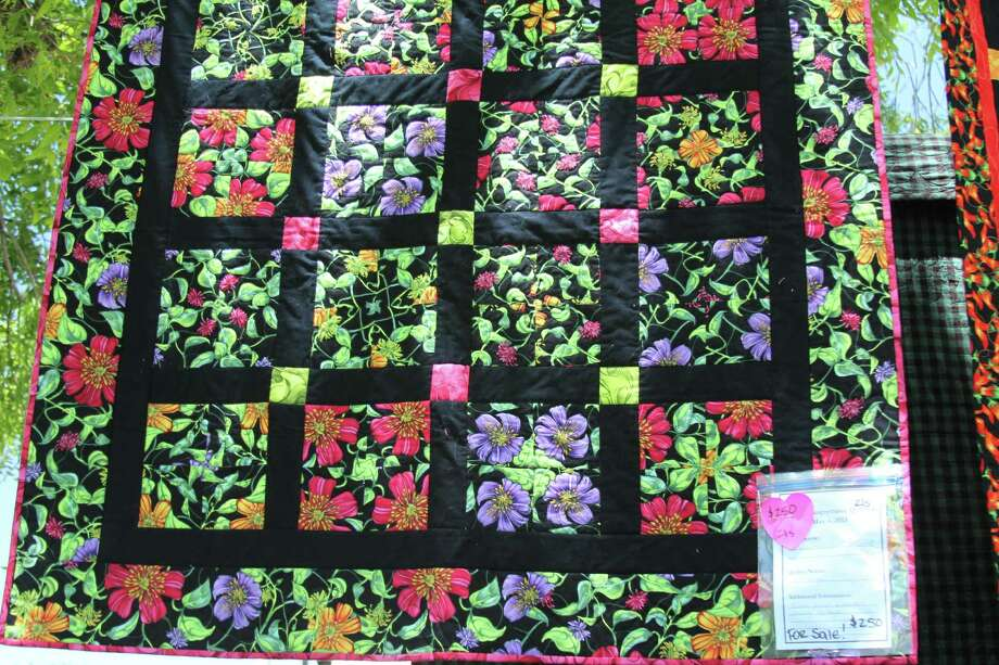 "Haupstrasse Quiltfest was held on Boerne's Main Plaza and throughout downtown Saturday, with quilt shows, sales and demonstrations and displays in retail store windows. ""Grandmother's Garden"" was sewn by Julie Ann Moore. Photo: Lauri Gray Eaton / Northwest Wee"