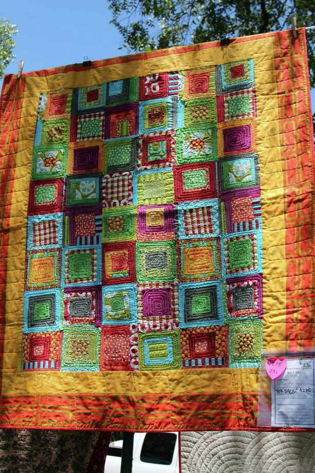 "Haupstrasse Quiltfest was held on Boerne's Main Plaza and throughout downtown Saturday, with quilt shows, sales and demonstrations and displays in retail store windows. ""Happy Fabric Hug"" was sewn by Julie Ann Moore. Photo: Lauri Gray Eaton / Northwest Wee"