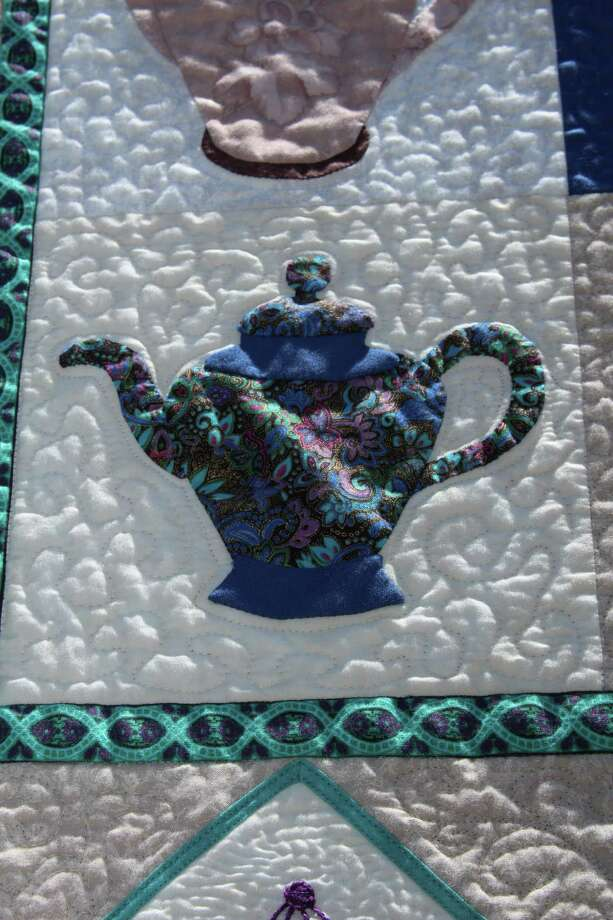 "Haupstrasse Quiltfest was held on Boerne's Main Plaza and throughout downtown Saturday, with quilt shows, sales and demonstrations and displays in retail store windows. ""My Little Teapots"" was sewn by Shirley Smith. This is a close-up of one section. Photo: Lauri Gray Eaton / Northwest Wee"