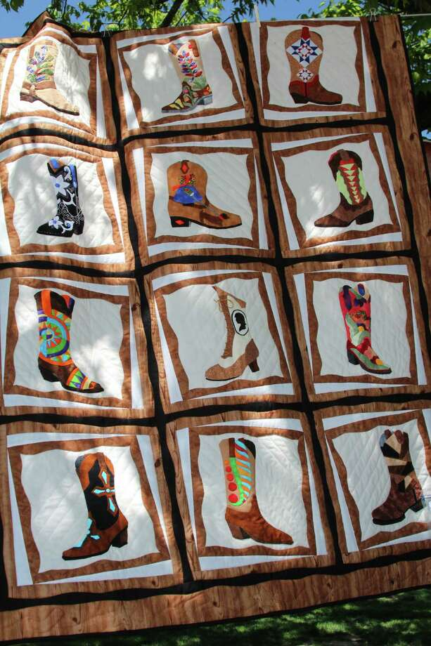 "Haupstrasse Quiltfest was held on Boerne's Main Plaza and throughout downtown Saturday, with quilt shows, sales and demonstrations and displays in retail store windows. ""Boots Galore"" was sewn by Bonnie Gates. Photo: Lauri Gray Eaton / Northwest Wee"