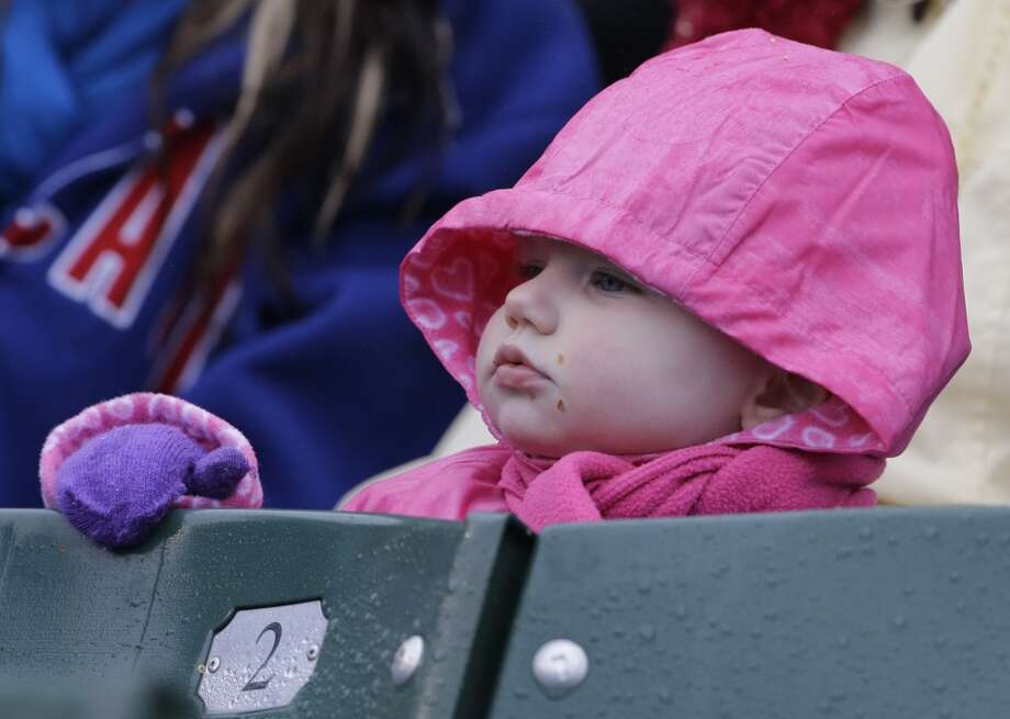A chilly baseball fan watches the San Francisco Giants play the Chicago Cubs in Chicago, Thursday, April 11, 2013.