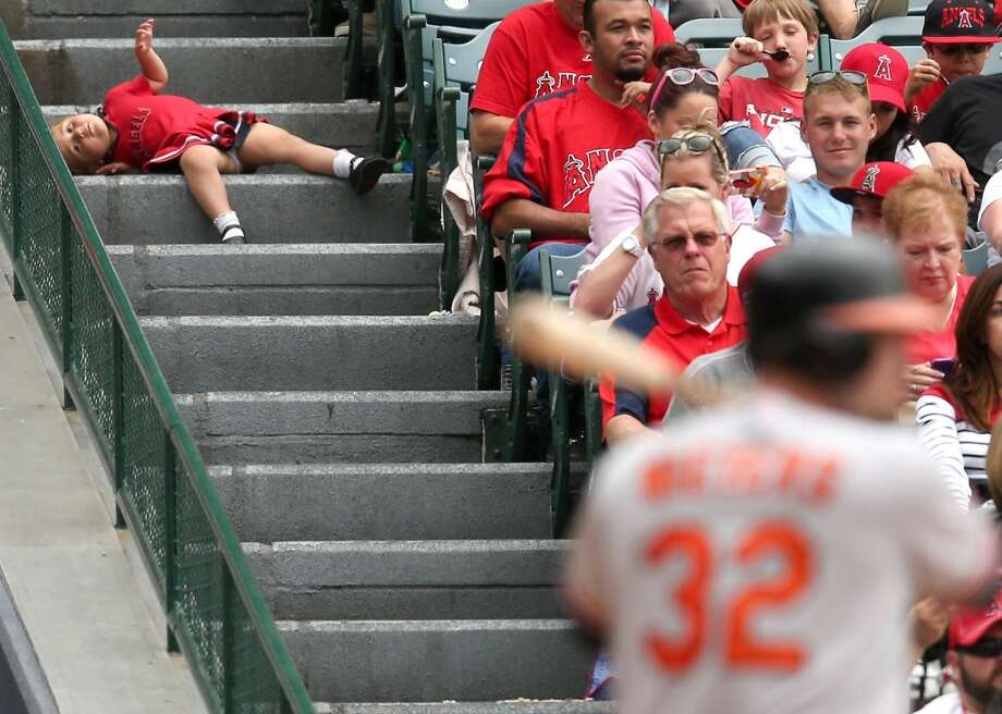 A young fan stretches out on the steps during the game between the Baltimore Orioles and the Los Angeles Angels of Anaheim at Angel Stadium of Anaheim on May 5, 2013 in Anaheim, California.