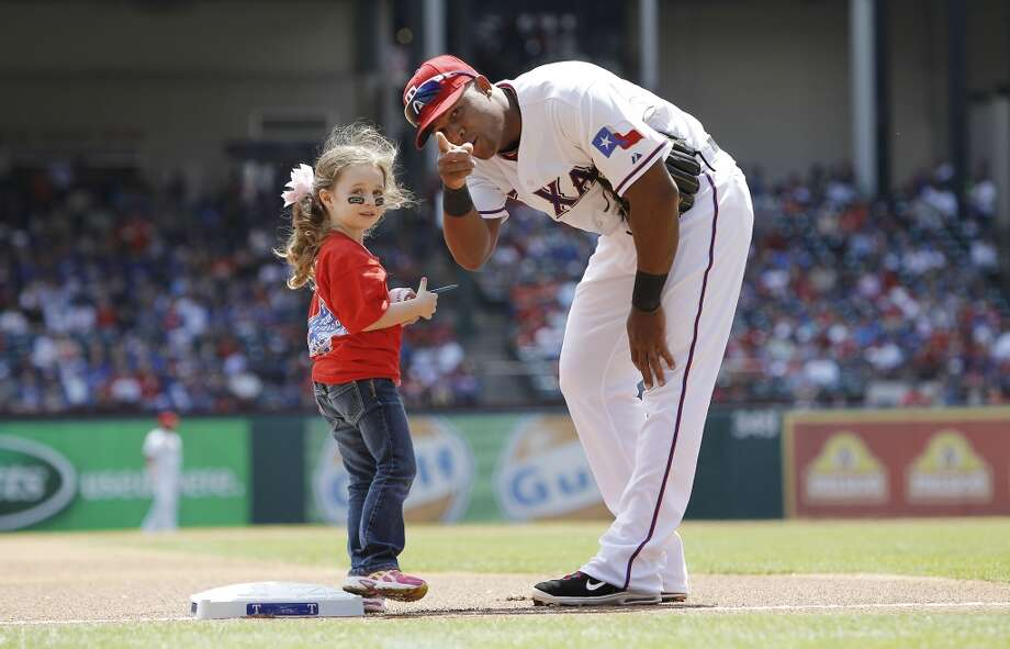Texas Rangers third baseman Adrian Beltre points to where a young fan should leave the field before the start of a baseball game against the Seattle Mariners.