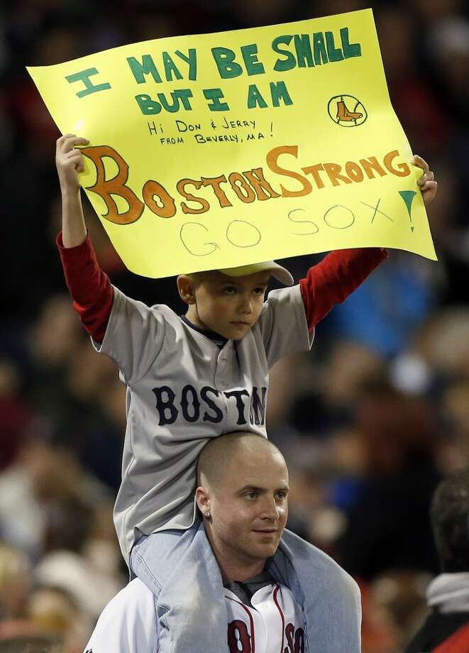 A young fan holds a Boston Strong sign in the sixth inning of a baseball game against the Houston Astros in Boston, Saturday, April 27, 2013.