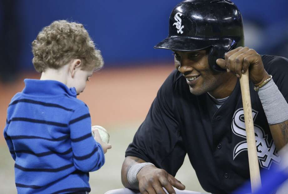 Alexei Ramirez of the Chicago White Sox gives a baseball to a young fan before an MLB game against the Toronto Blue Jays on April 15, 2013 at Rogers Centre in Toronto, Ontario, Canada.