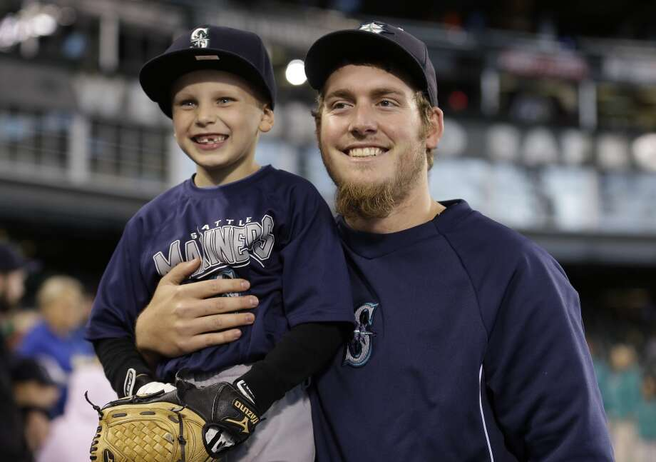 Seattle Mariners pitcher Brandon Maurer poses for a fan photo with Laken Cochran, 6, of Castle Rock, Wash.