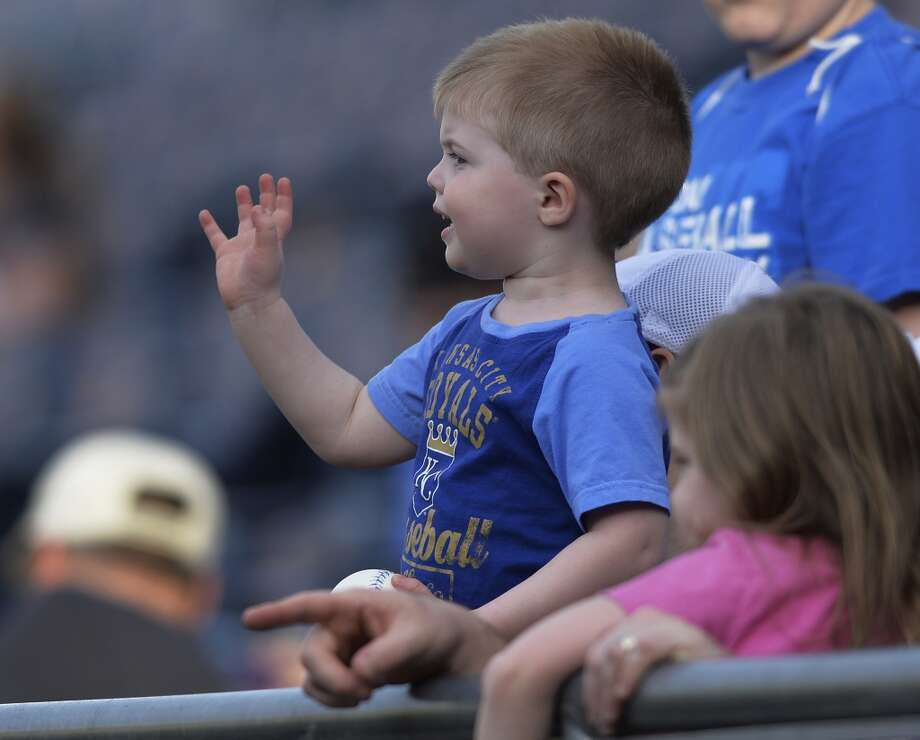 One of the Royals' small fans waves to the players during warm-ups before a baseball game between the Kansas City Royals and Cleveland Indians, Monday, April 29, 2013, in Kansas City, Mo.