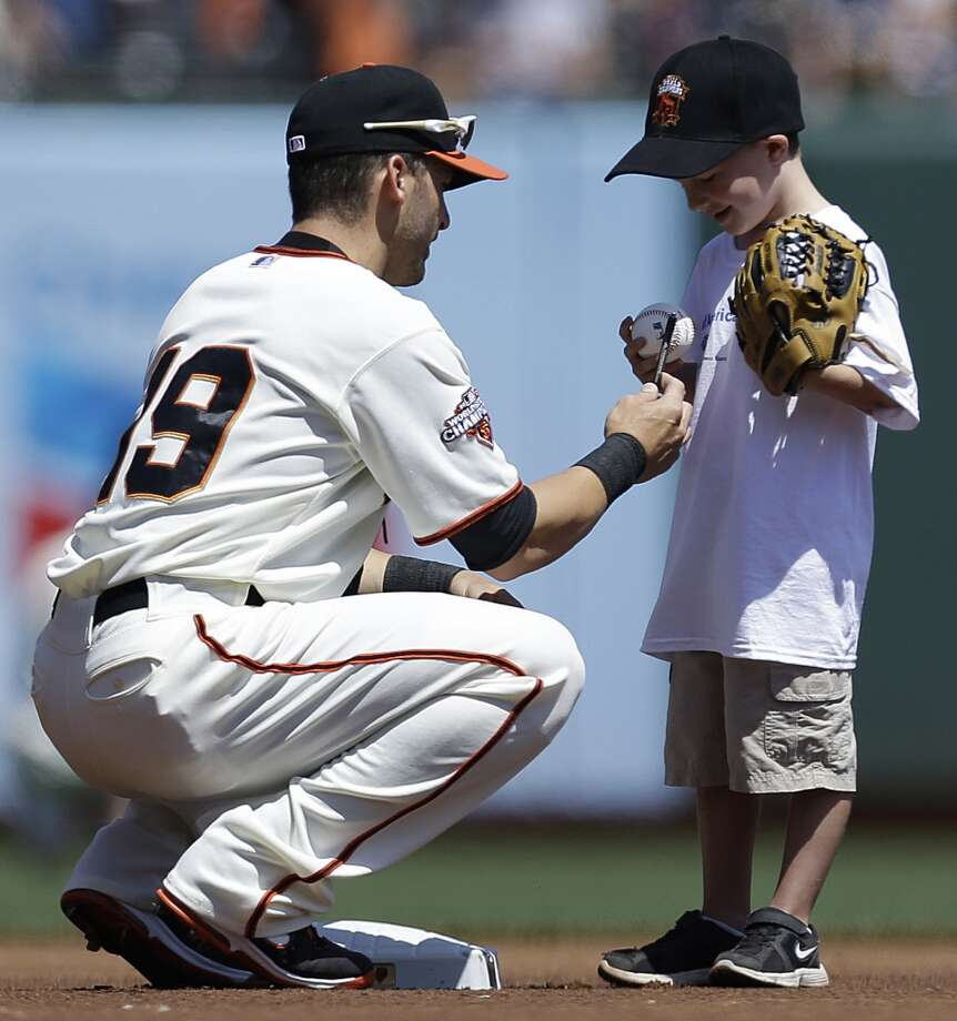 San Francisco Giants' Marco Scutaro signs an autograph for a young fan prior to the baseball game against the San Diego Padres.