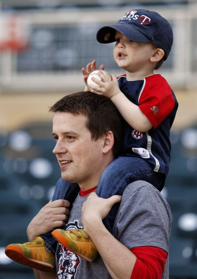 Minnesota Twins fans Brian Meyer and his son James, 2, of Bloomington, Minn., watch the Twins during warmups.
