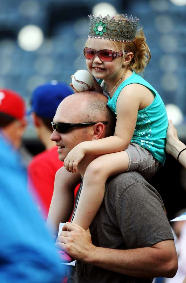 Kansas City Royals fan Billy Cole holds his daughter, 4-year-old Jenna, as they watch batting practice before a baseball game against the Tampa Bay Rays at Kauffman Stadium in Kansas City, Mo.