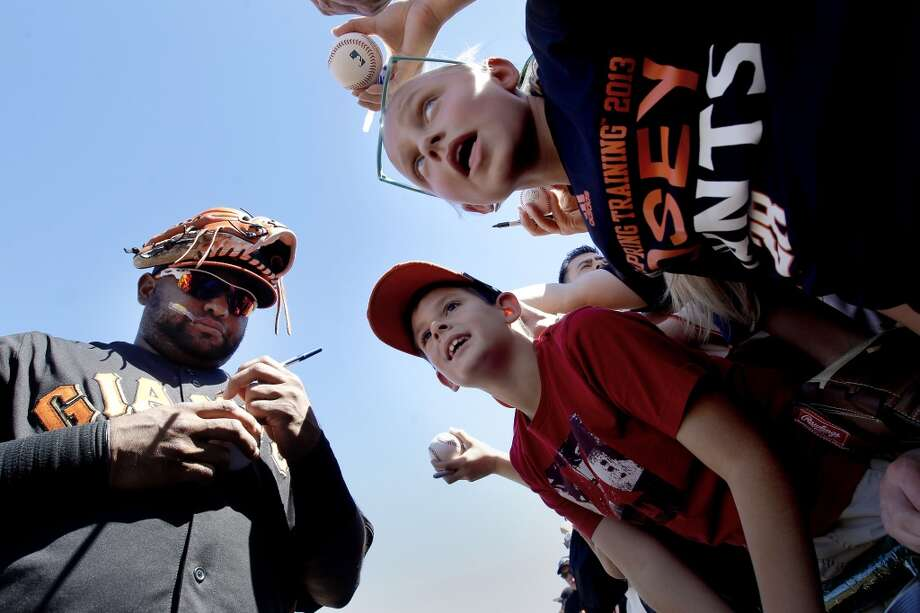 Giants' Pablo Sandoval signs autographs for fans before the start of the game.