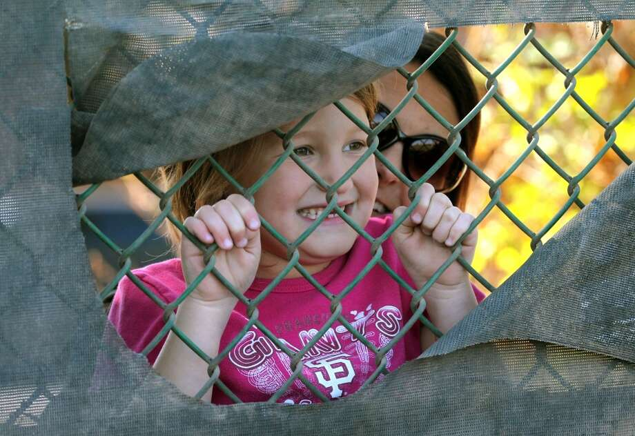 San Francisco Giants fan McKenna Alvarado 7 from Mesa Ariz, gets help reaching a hole in the fence at Scottsdale Stadium from her mother Airin Alvarado during batting practice at spring training Monday, Feb. 18, 2013, in Scottsdale, Ariz.