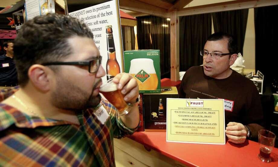Anthony Giardina, right, of Palm Breweries talks with Rafael Guzman at a retailer trade show at the Faust Distributing Center in Houston. Photo: Thomas B. Shea / © 2013 Thomas B. Shea