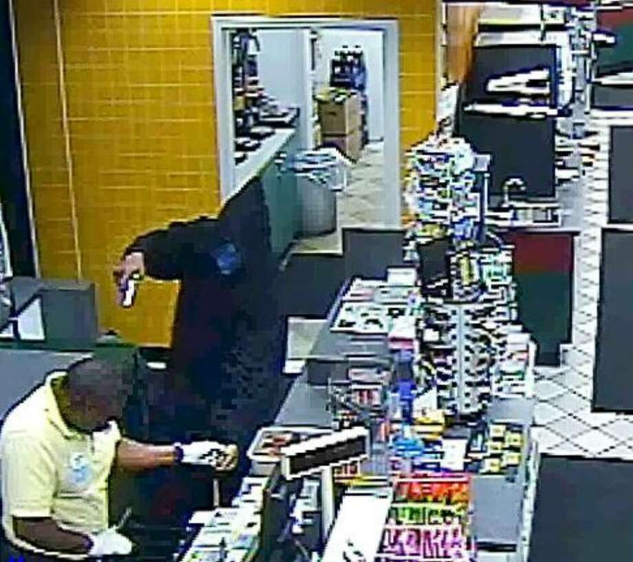 A still frame from the video which was released by the Greenwich police dept., shows the Nov. 21st, 2009  armed robbery and shooting at the Mobil on the Run gas station on East Putnam Avenue in Old Greenwich in which the hooded suspect with the gun wounded the store employee shown at left. Photo: Contributed Photo / Greenwich Time Contributed