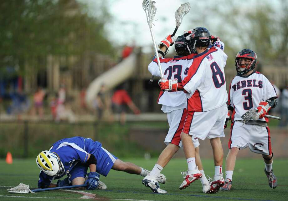 New Fairfield's Ben Gioia (23), Kyle Lutinski (8) and Ryan Lewis (3) celebrate a goal as Brookfield's Joseph Dixon falls to the turf during New Fairfield's 15-12 boys lacrosse win over Brookfield at New Fairfield High School in New Fairfield, Conn. on Tuesday, May 7, 2013. Photo: Tyler Sizemore / The News-Times