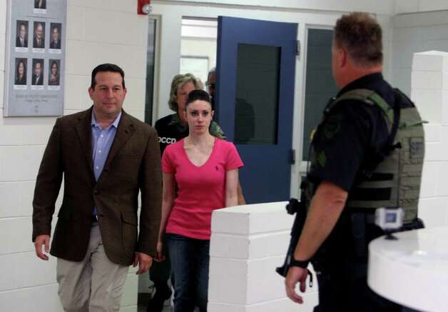 Casey Anthony, center, walks out of the Orange County Jail with her attorney Jose Baez, left,  during her release in Orlando, Fla., early Sunday, July 17, 2011.  Anthony was acquitted last week of murder in the death of her daughter, Caylee. (AP Photo/Red Huber, Pool) Photo: Red Huber, POOL / Pool Orlando Sentinel