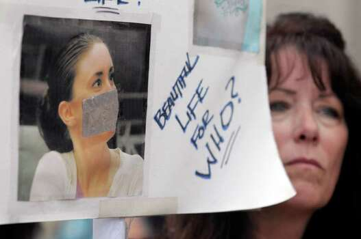 Lori Richards, right, of Daytona Beach, Fla., protests outside the Orange County Courthouse during the sentencing hearing for Casey Anthony in Orlando, Fla., Thursday, July 7, 2011.  Judge Belvin Perry sentenced  Anthony to four years for lying to investigators but says she can go free in late July or early August because she has already served nearly three years in jail and has had good behavior. While acquitted of killing and abusing her 2-year-old daughter Caylee, Anthony was convicted of four counts of lying to detectives trying to find her daughter in July 2008. (AP Photo/Phelan M. Ebenhack) Photo: Phelan M. Ebenhack