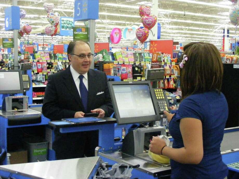 San Antonio Hispanic Chamber of Commerce President Ramiro Cavazos makes a purchase from Walmart associate Jazmin Benedicto during the store's May 1 opening. Photo: Jeff B. Flinn / NE Herald