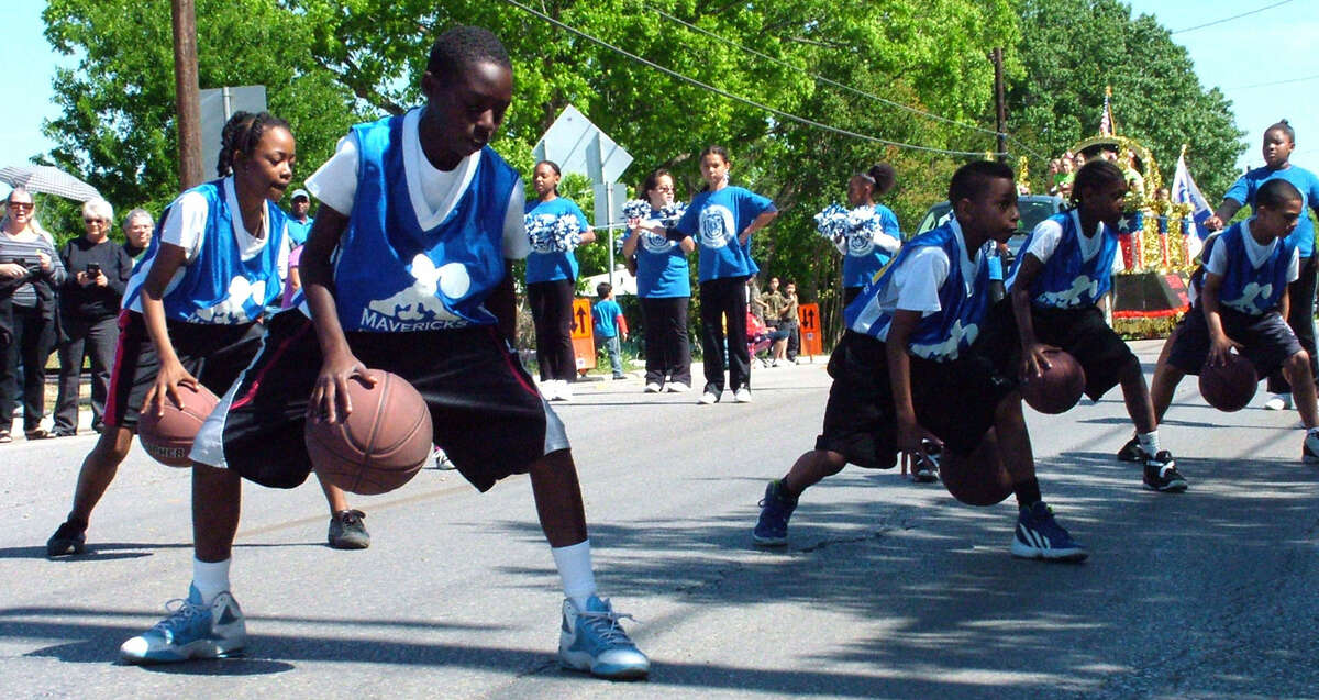 Donnie Harris (foreground), a fifth-grade student at Masters Elementary, goes through the paces of a basketball drill with teammates on the Masters' Dribble Team, Cheer Squad and Twirlers Saturday during the annual HoboFest parade in Kirby.