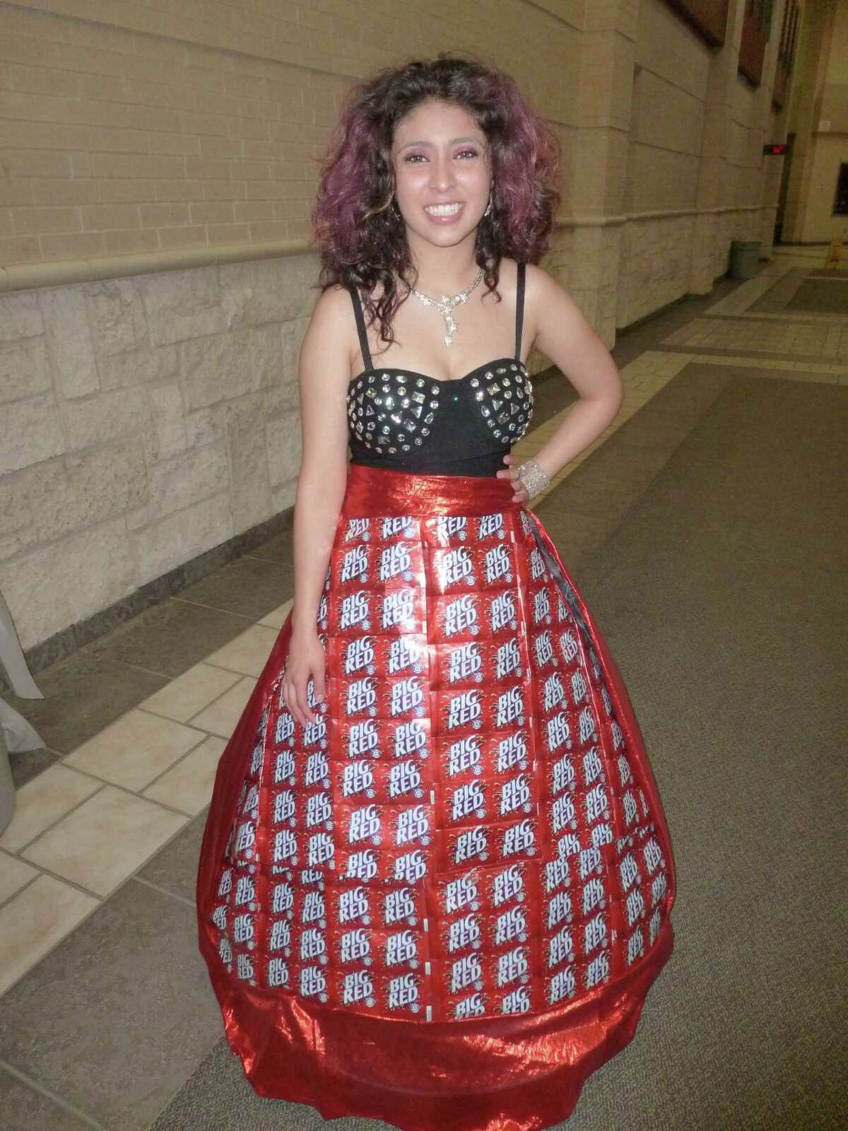 Left, Melissa Ronquillo models Wagner classmate Ehrika Watson's Big Red dress, fashioned from more than 200 soda cans. Right, Kimi Fernandez steps out in her paper plate wedding dress in the May 2 Wagner Recycled Fashion Show.