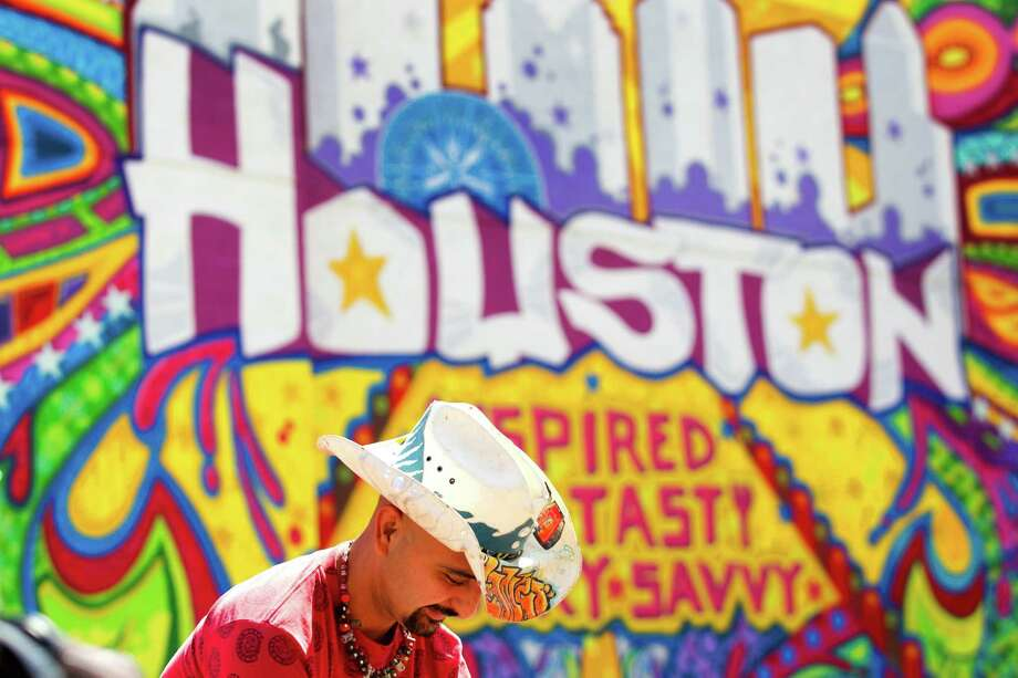 "Artist GONZO247 prepares to unveil his mural ""Houston Is"" during the kickoff of ""Houston Is Inspired"" campaign Tuesday, May 7, 2013, in Houston. GONZO247 said he spent a month working on the mural, using 250 cans of spray paint. Photo: Brett Coomer, Houston Chronicle / © 2013 Houston Chronicle"