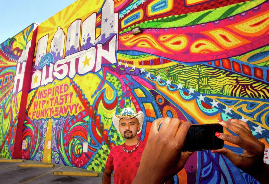"Artist GONZO247 poses for a photo in front of his mural ""Houston Is"" at the corner of Preston and Travis during the kickoff of ""Houston Is Inspired"" campaign Tuesday, May 7, 2013, in Houston. Photo: Brett Coomer, Houston Chronicle / © 2013 Houston Chronicle"