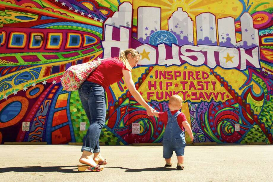 "Jill Jarvis, left, walks with her son, James, in front of a mural by GONZO247 named ""Houston Is"" in the parking lot at the intersection of Preston and Travis during the kickoff of ""Houston Is Inspired"" campaign Tuesday, May 7, 2013, in Houston. Photo: Brett Coomer, Houston Chronicle / © 2013 Houston Chronicle"