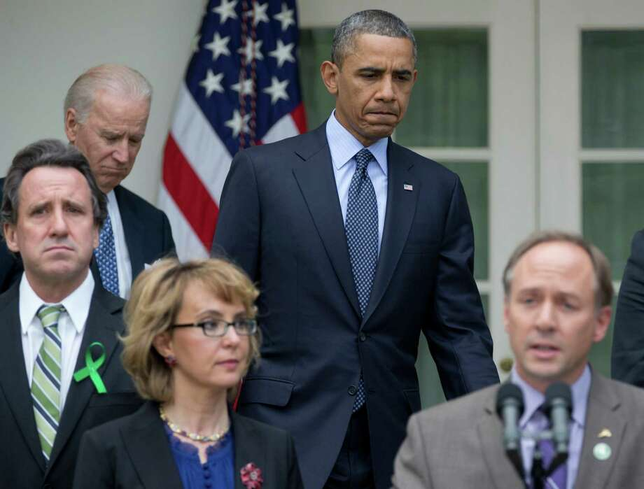 President Barack Obama and Vice President Joe Biden arrive as Mark Barden, the father of Newtown shooting victim Daniel, lower right, speaks during a news conference in the Rose Garden of the White House, Wednesday, April 17, 2013, in Washington, about measures to reduce gun violence and a bill to expand background checks on guns that was defeated in the Senate. They are joined by joined by former Rep. Gabby Giffords, second from left, and Newtown family members Neil Heslin, father of Jesse Lewis.  (AP Photo/Carolyn Kaster) Photo: Carolyn Kaster, Associated Press / AP