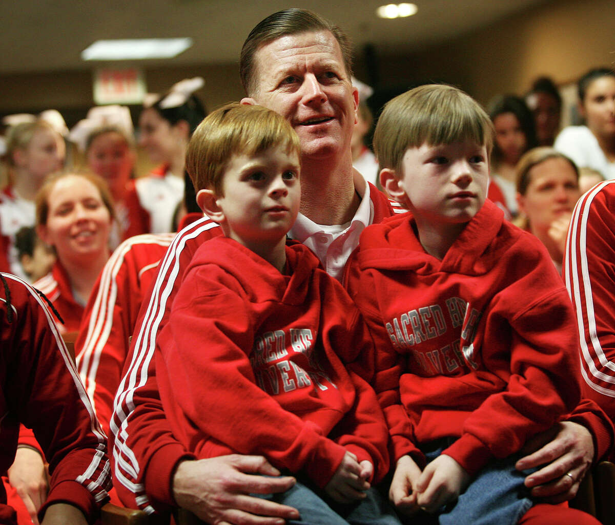 Sacred Heart women's basketball Coach Ed Swanson, holding sons Matthew, 4, and Connor, 5, Callan Taylor, and Katie Shepard awaits the announcement of his team's seeding in the NCAA Women's Basketball Tournament on Monday, March 12, at Sacred Heart University in Fairfield.