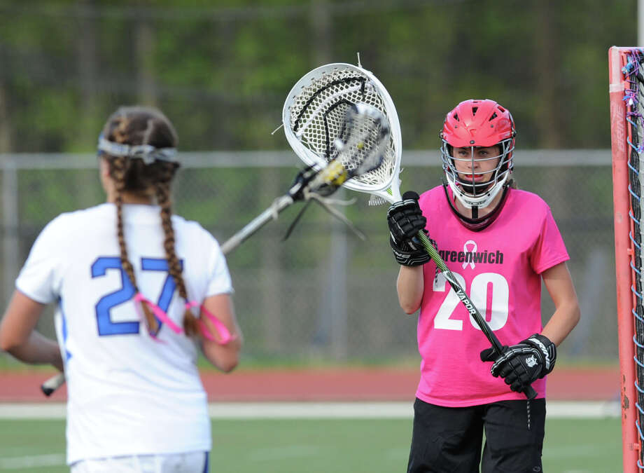 At left, Taylor Hardison of Darien (# 27) approaches the net being defended by Greewich golaie Kylie Ginsberg (# 20) during the girls high school lacrosse match between Darien High School and Greenwich High School at Darien, Tuesday afternoon, May 7, 2013. Darien won the match 17-9. Photo: Bob Luckey / Greenwich Time
