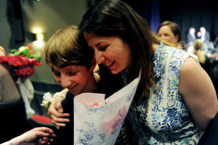 Michael Blieberg, a student of Eastern Middle School gave flowers to a distinguished teacher Esra Murray, for his favorite teacher during the Distinguished Teachers Awards at Western Middle School, in Greenwich, Tuesday, May 7, 2013. Photo: Helen Neafsey / Greenwich Time