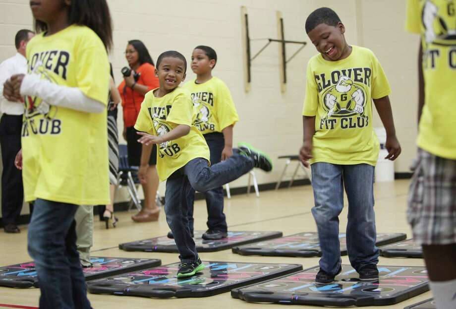 First grader Ashton Webber, 6, horseplays with his brother Frederick Webber, 8, as they join the third grade class showcasing the new DanceRevolution Classroom Edition video game. Photo: Mayra Beltran / © 2013 Houston Chronicle